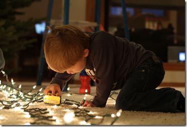 ребенок играющий с новогодней гирляндой