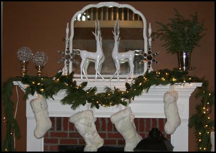 рождественские гирлянды и сапожки для подарков на камине