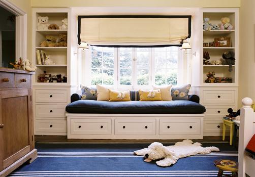 Диван с синими подушками под окном между стеллажами в детской