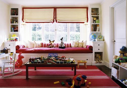 Диван с малиновыми подушками под окном между стеллажами
