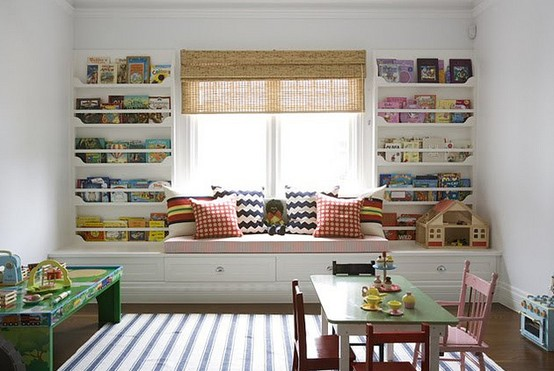 Диван под окном между стеллажами в белой детской полосатые и клетчатые подушки