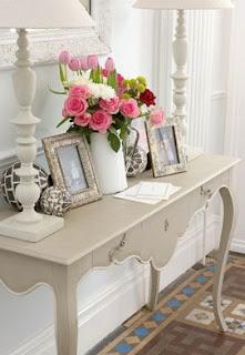 белая консоль. белые настольные лампы, серебряные фоторамки и розы