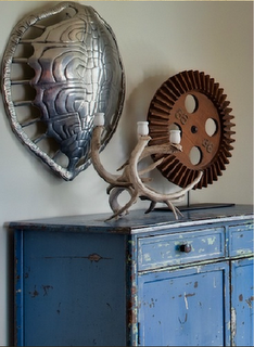 декоративная композиция на стене и подсвечник над старым синим комодом