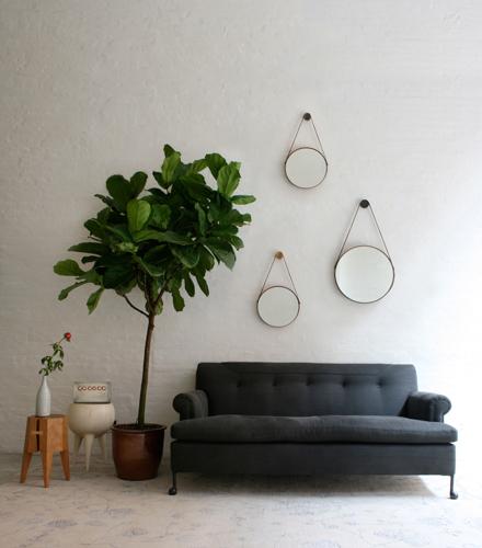 диван и деревце на фоне белой кирпичной стены в офисе