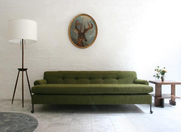 диван на фоне белой кирпичной стен в офисе мебельной компании