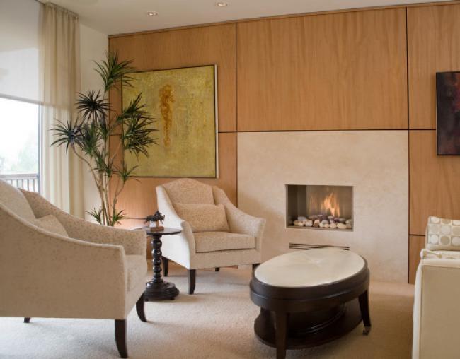 газовый камин в стене, обшитой светлыми деревянными панелями и белые кресла
