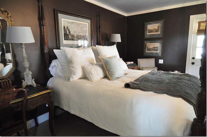 Темно-коричневые стены и белые плинтуса в маленьком помещении спальни