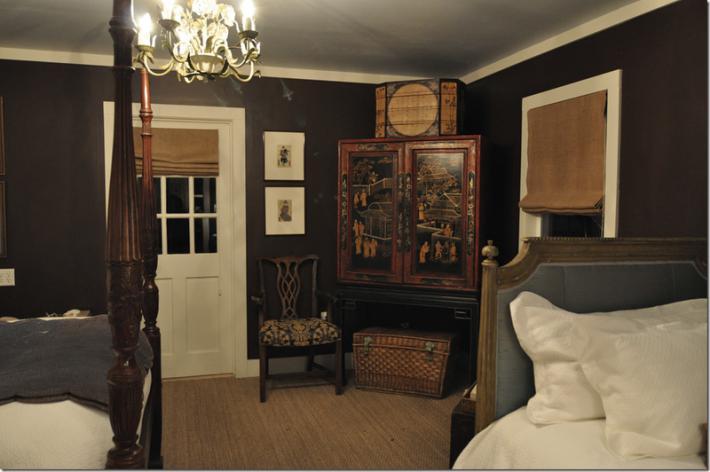 Темно-коричневые стены, белые плинтуса и двери в спальне маленького помещения